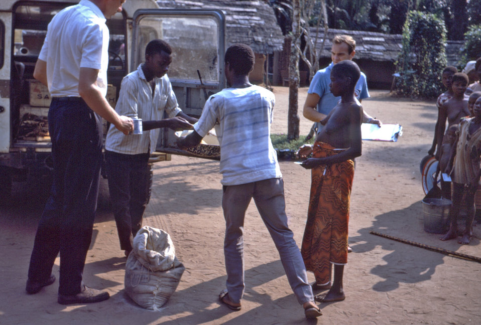 This 1968 photograph showed former CDC Director, William H. Foege, M.D., M.P.H., assisting in the distribution of dry food rations after the
