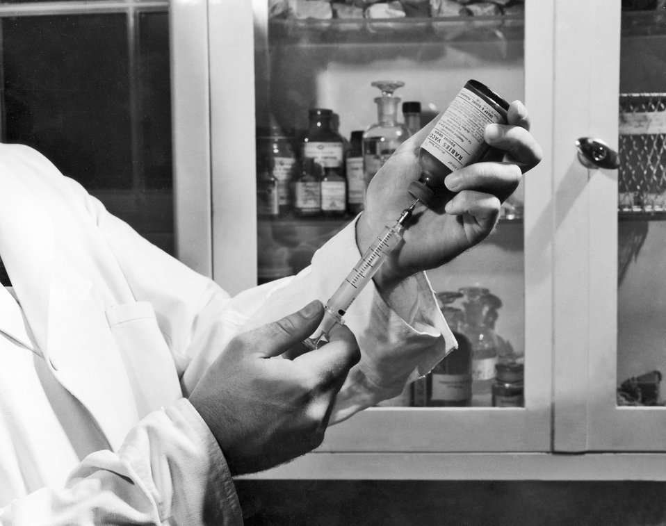 This photograph shows a Centers for Disease Control laboratorian as he was filling a syringe with rabies vaccine that had been obtained from