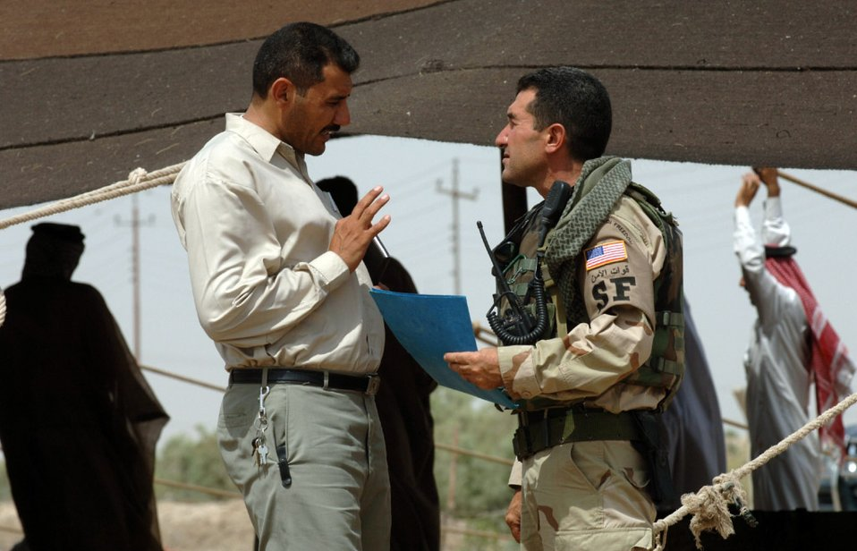 IRAQ -- Sam (right) talks to a local man. The Arab linguist talks to many leaders in the area, listening to their concerns and sharing ideas