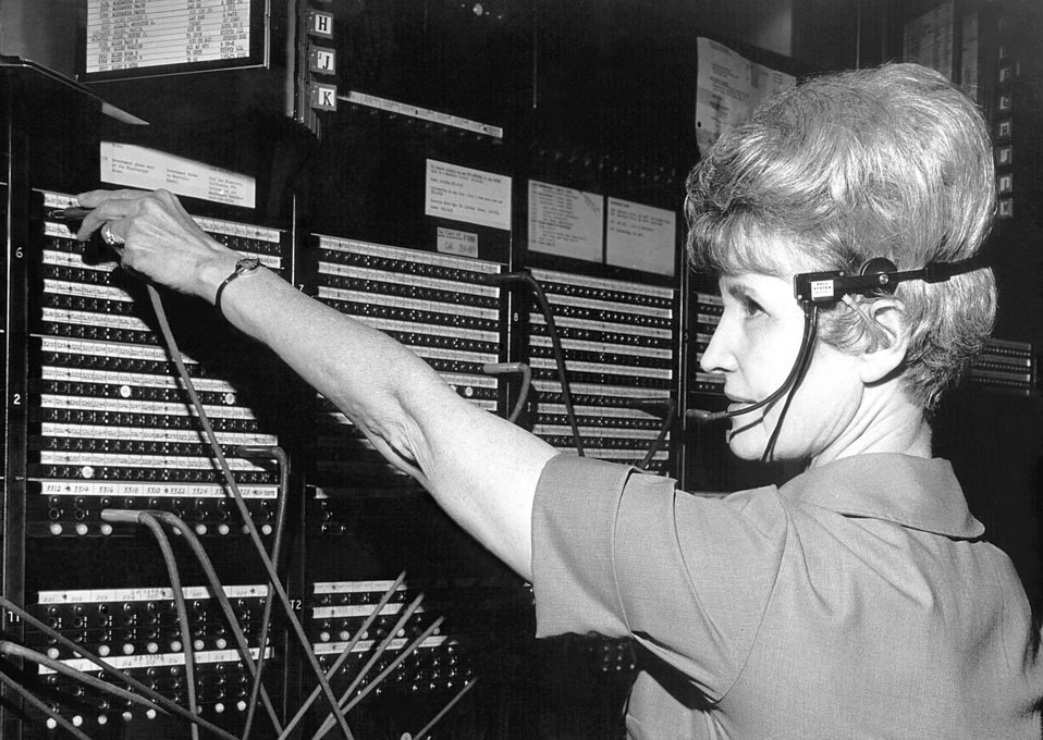 This historic 1974 photograph depicts a CDC telephone operator seated at a switchboard, and wearing a traditional headset.