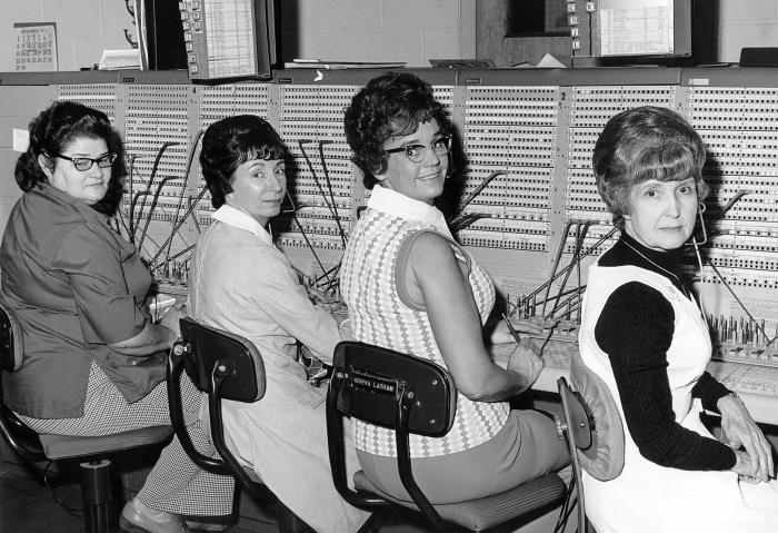 This historic 1974 photograph depicts a number of CDC telephone operators in front of a traditional switchboard.