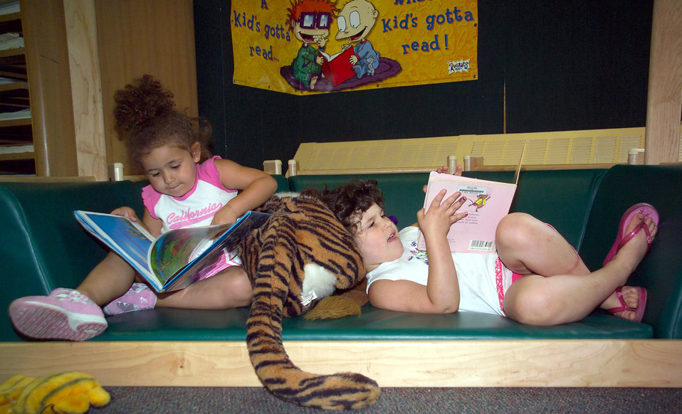 Two young girls reading books
