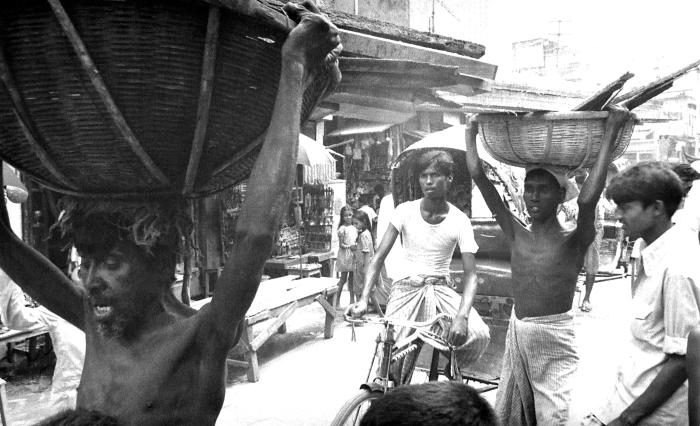This photograph depicted the hustle-bustle of a typical Bangladesh street scene.  In this instance, a number of men were carrying lumber and