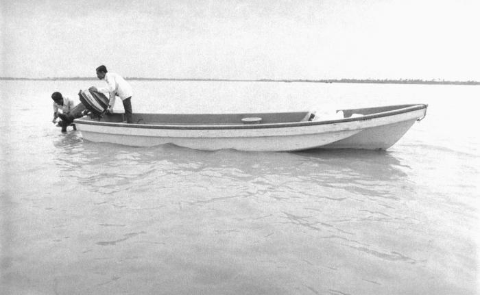 This photograph depicted two Bangladesh men in a motorboat whose engine was being repaired by one of the men while he stood alongside the bo
