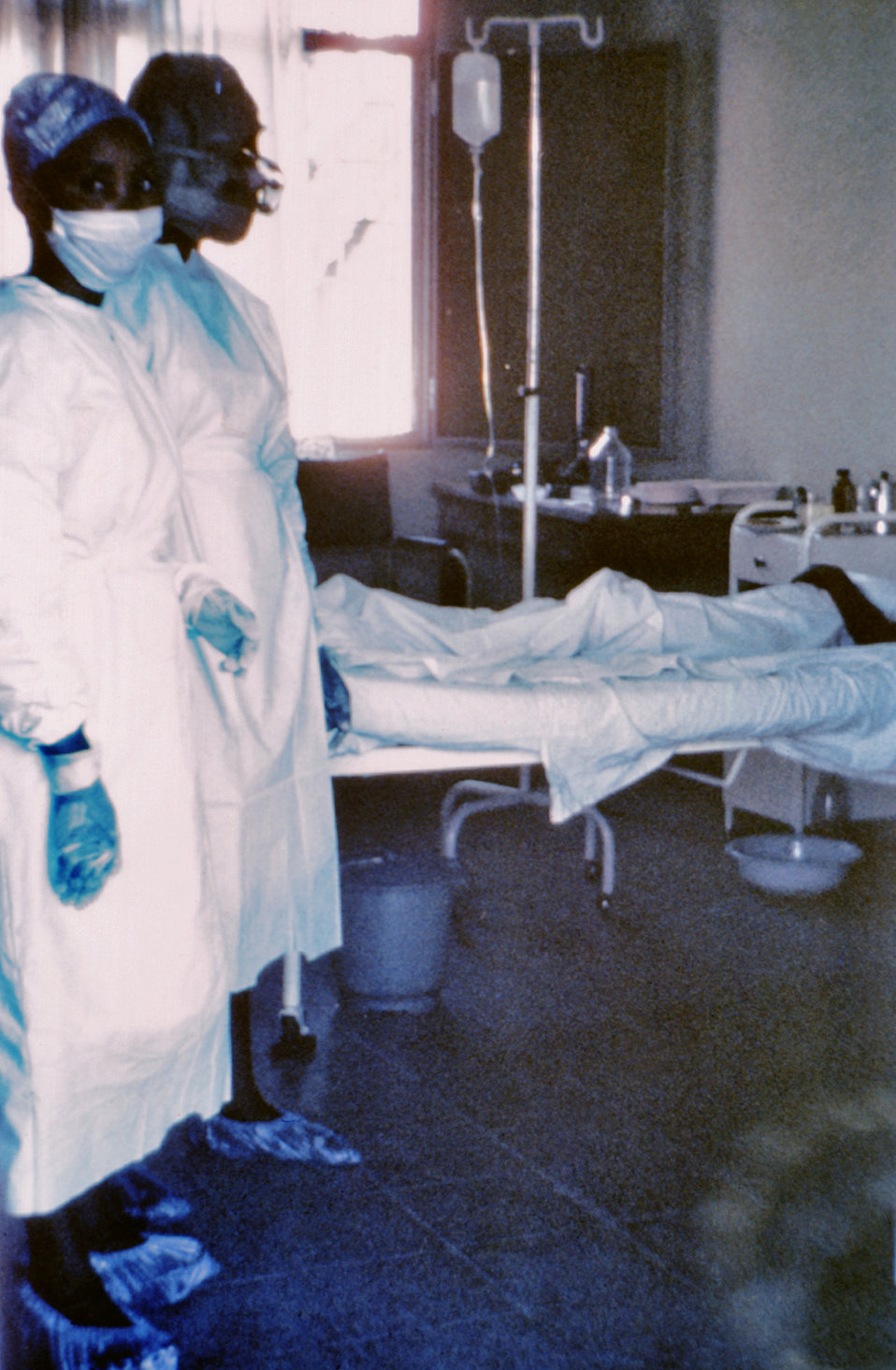This 1976 photograph shows two nurses standing in front of Ebola case #3, who was treated, and later died at Ngaliema Hospital, in Kinshasa,