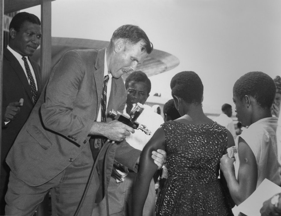 This was Dr. Stan Foster, EIS Officer, Class of 1962 (Cntr), as he administers a smallpox vaccination to a Nigerian woman, 1967.
