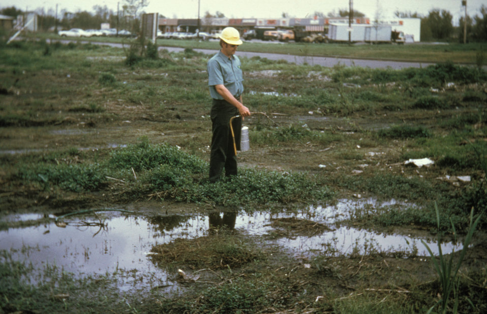 This photograph shows a man using a hand-carried compressed air sprayer apply 'larviciding' oil to mosquito breeding pools.