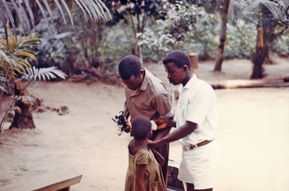 This late 1960s photograph shows a child being vaccinated for measles and smallpox in a relief camp outside of a war zone in Nigeria. These