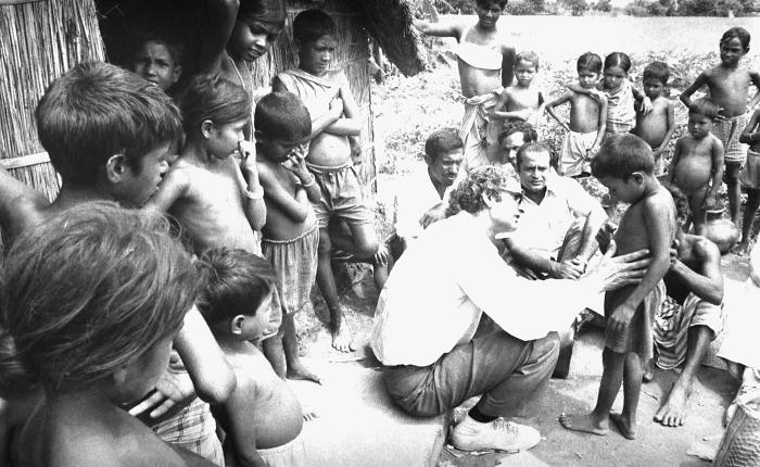 This image depicted World Health Organization (WHO) epidemiologist Dr. Hari Mehta (center, wearing glasses), examining village children for