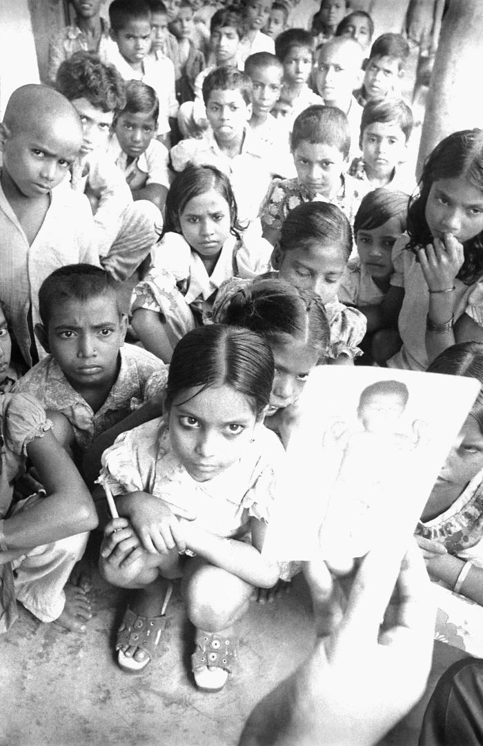 This 1975 photograph depicted an eradication team member showing school children the image of a child with smallpox, which accompanied the s