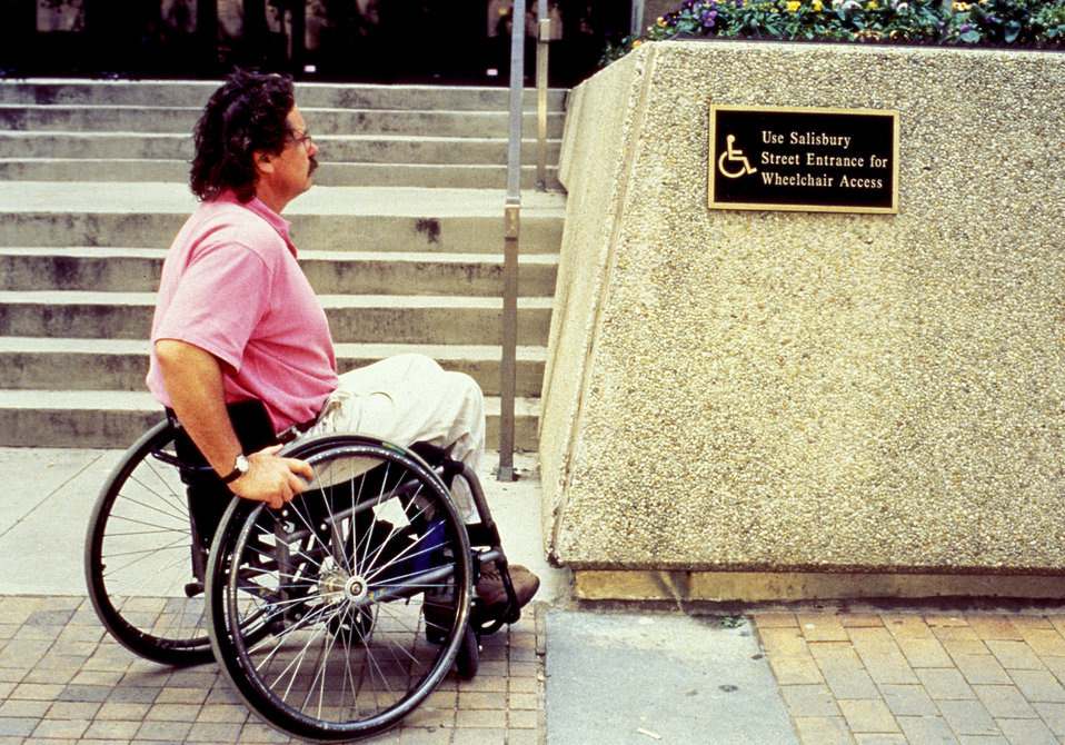 The wheelchair-seated man depicted in this photograph, whose mobility had been reduced, was shown reading a sign indicating to him that whee