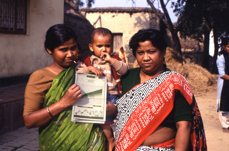 This 2000 photograph depicted a mother holding her child, while displaying a polio vaccination record that indicated the child having been p