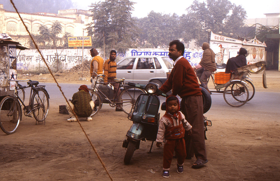 This 2000 photograph depicted a father who'd brought his child to this Indian polio vaccination center on his motor scooter. Often fathers b