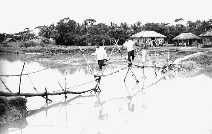 This 1975 image depicted a bamboo-constructed bridge used as an integral tool in daily Bangladesh village life, and was another of the route