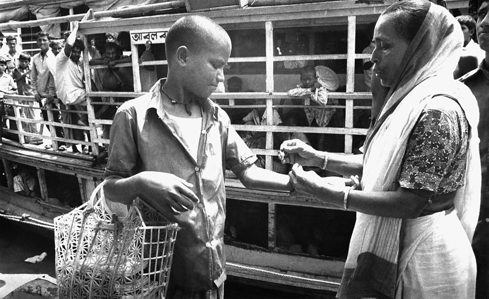 On this day in 1975, this boy was being vaccinated by a local volunteer smallpox eradication team member as he was getting ready to board a