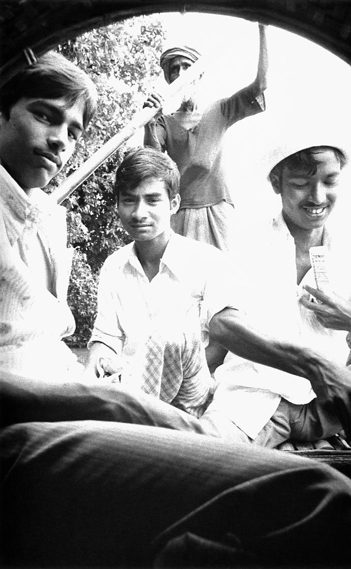 Seated on the right next to two fellow passengers, this Bangladesh volunteer smallpox eradication team vaccinator was traveling by river boa