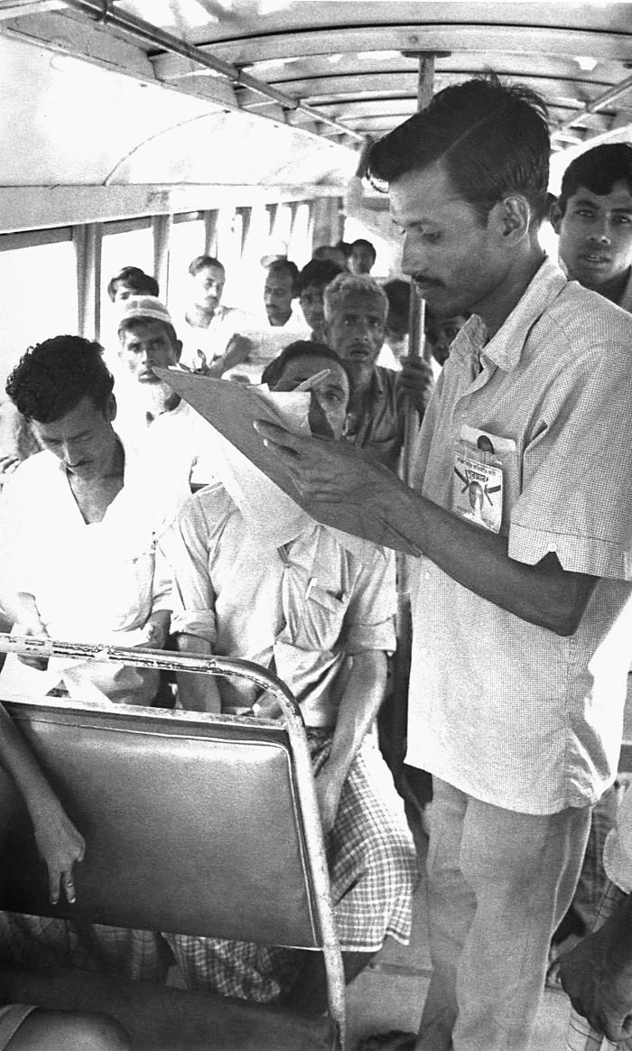 This 1975 image depicted a community volunteer smallpox eradication team member collecting data while inside a bus, regarding possible small