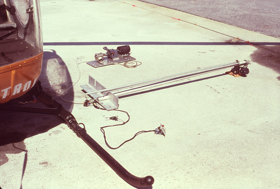 This photograph depicts a Hughes helicopter that had been outfitted with an ultra-low volume (ULV) insecticidal fog generator enabling it to