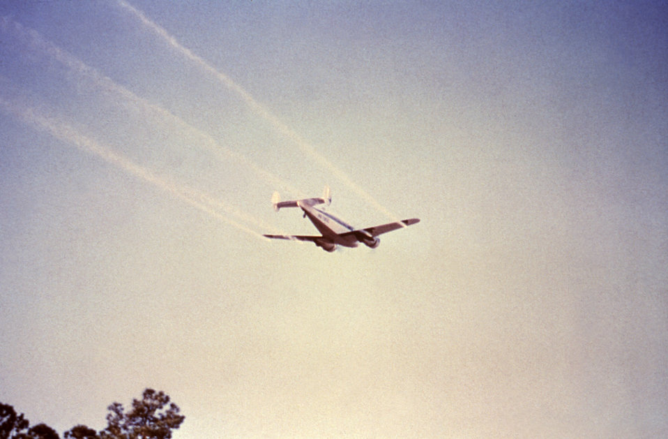 This 1981 photograph depicts a twin-engine Beechcraft dispersing its payload of ultra-low volume (ULV) insecticidal fog in order to control