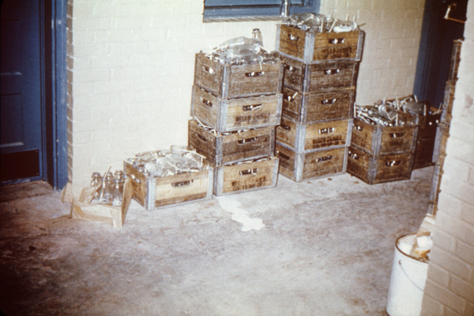 These crates of open milk bottles stored in a migrant workers' camp are shown in violation of health inspection codes.