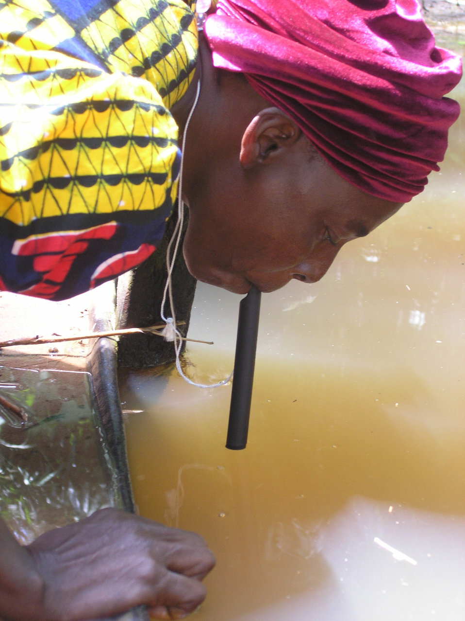 This 2002 image depicts a Nigerian woman drinking water directly from a local pond through a pipe filter. Similar to a straw, pipe filters a