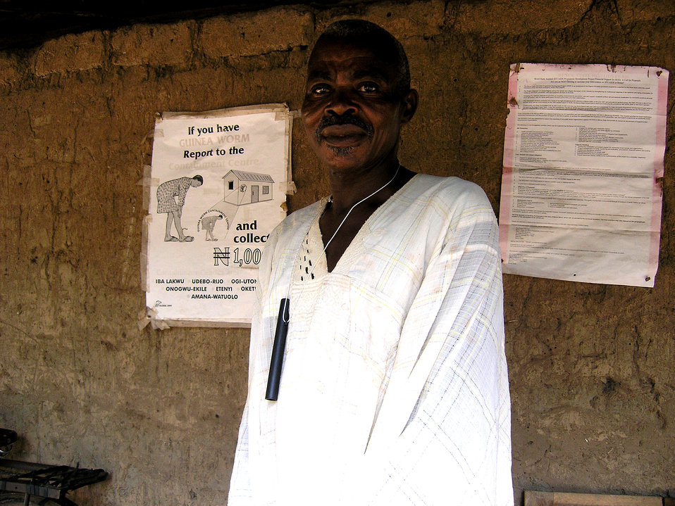 This 2004 photograph depicts a Nigerian man inside a Guinea worm containment center, wearing a pipe filter around his neck through which he