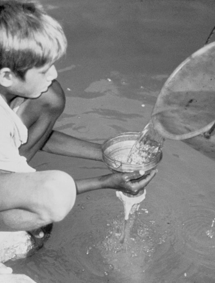 This 1990 photograph depicted a child who was holding a strainer composed of a metal funnel, and a piece of filter cloth. Water taken from t