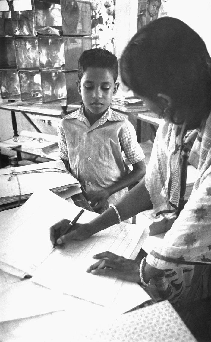 This 1975 image depicted a local Bangladesh smallpox eradication team volunteer questioning a community child, and entering the discussion d