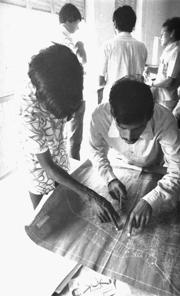 This 1975 image depicted two local Bangladesh men who were working as smallpox eradication team volunteers, as they were analyzing a 'Contai