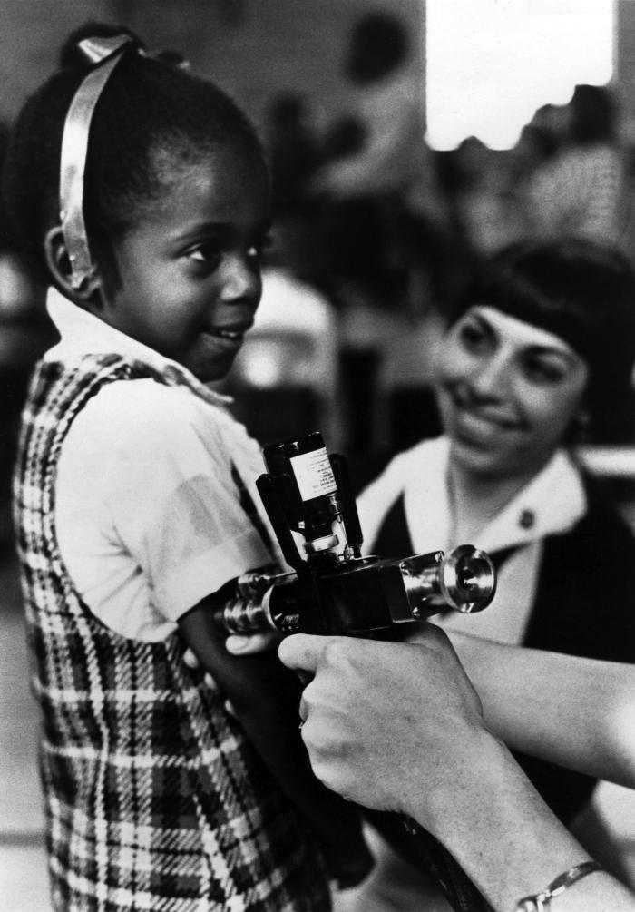 This photograph, used in a public health awareness campaign in the 1980s, shows a female child receiving a vaccination delivered by a jet in
