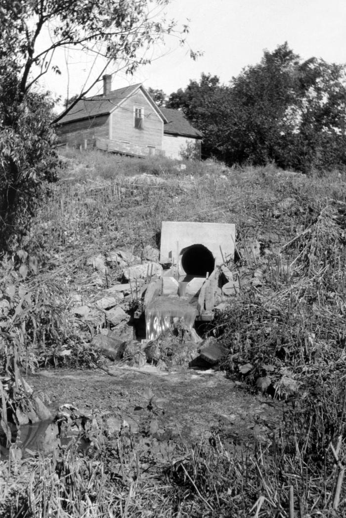This historic August, 1932 photograph depicted a sewer outlet on the banks of the Red River at First Street in Fargo, North Dakota. Raw sewa