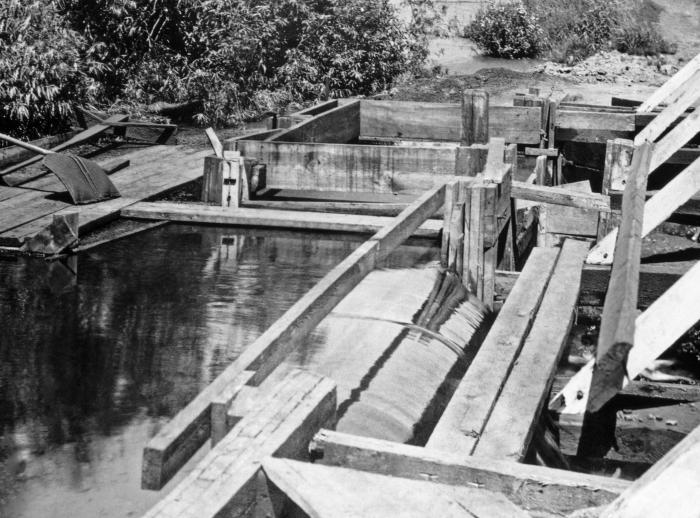 This historic 1929 photograph showed a coke plant sewer outlet into the St. Louis River at Morgan Park, Minnesota, near Duluth. A weir was i