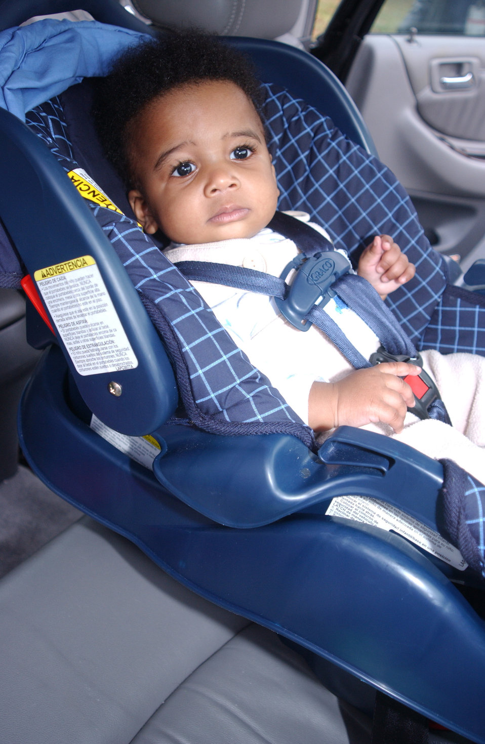 This 2004 photograph shows an infant who has been properly positioned, and buckled into a rear-facing infant-only car seat. For example, not