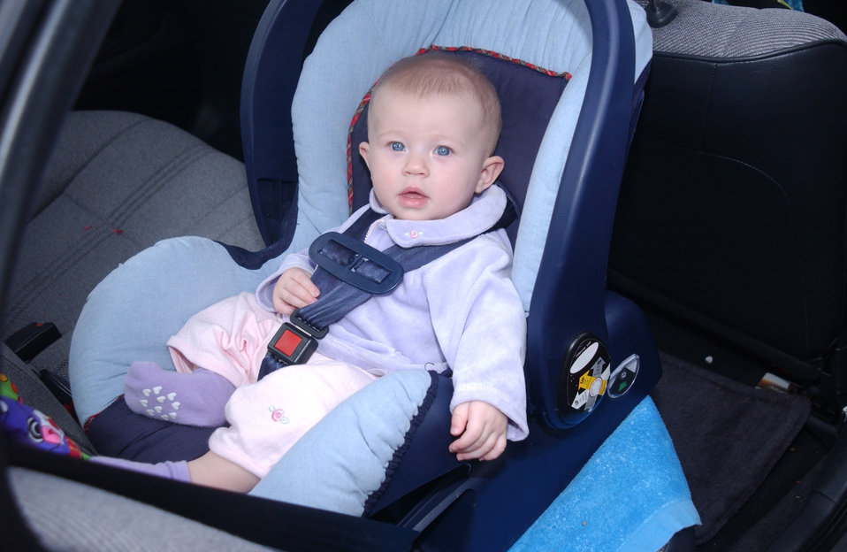 This 2004 photograph shows an infant who has been properly positioned, and buckled into a rear-facing car seat. For example, notice the harn
