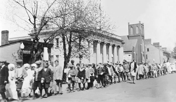 This historic photograph showed school children accompanied by adults, as they were marching during an observance of 'Child Health Day' in t