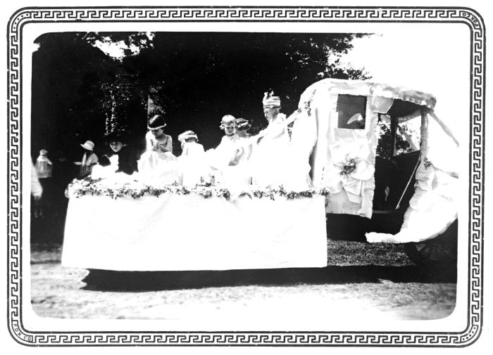 In this historic photograph, school children can be seen aboard a parade float in the state of Texas, during a celebration marking the obser