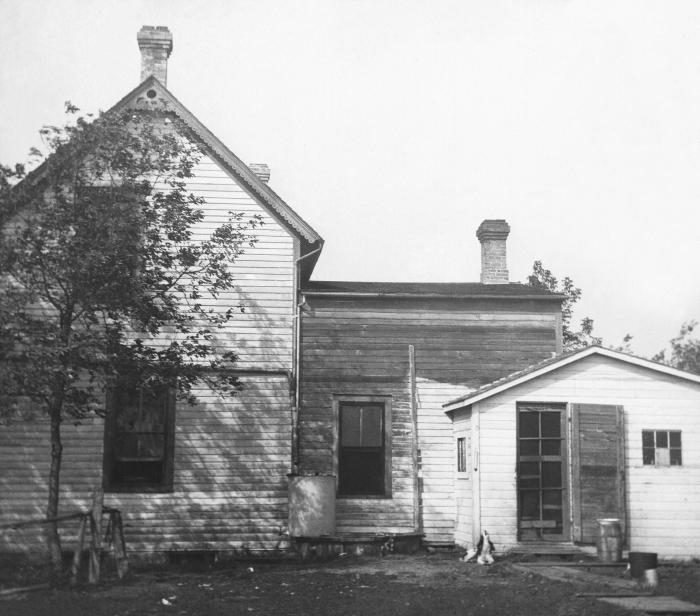 In this historic 1909 photograph, an improperly constructed cistern could be seen located adjacent to a typical Minnesota farm residence. It