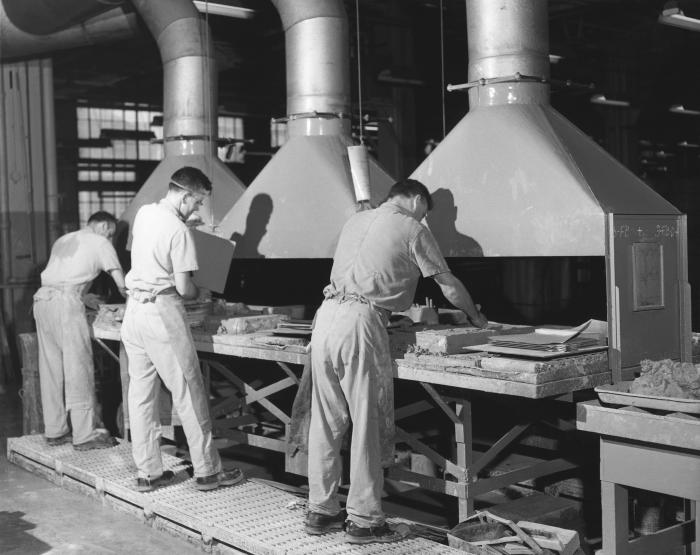 The three industrial workers depicted in this historic image, were working under ventilated hoods as lead pasters, in the battery manufactur