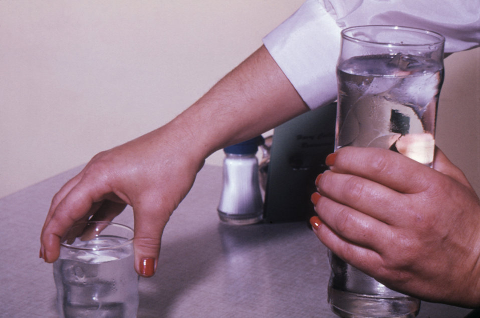 This photograph shows how a food and beverage server can contaminate clean dishware by handling the rims of beverage glasses.