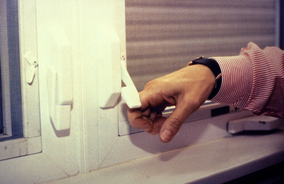 The adult's hand in this 1995 image was shown opening a casement window lock, which was operated by an up and down movement of a lever with