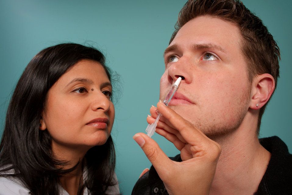 This 2009 image depicts a healthcare practitioner as she was administering the H1N1 live attenuated intranasal vaccine (LAIV) to a male reci