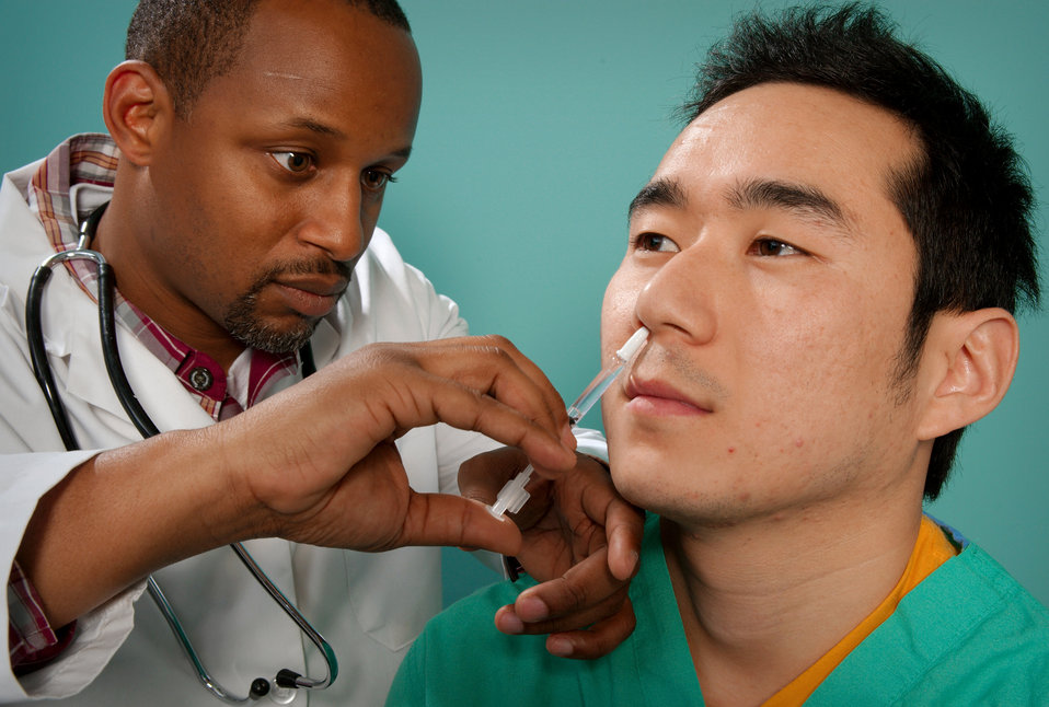 This 2009 image depicts a healthcare practitioner as he was administering the H1N1 live attenuated intranasal vaccine (LAIV) to an Asian man