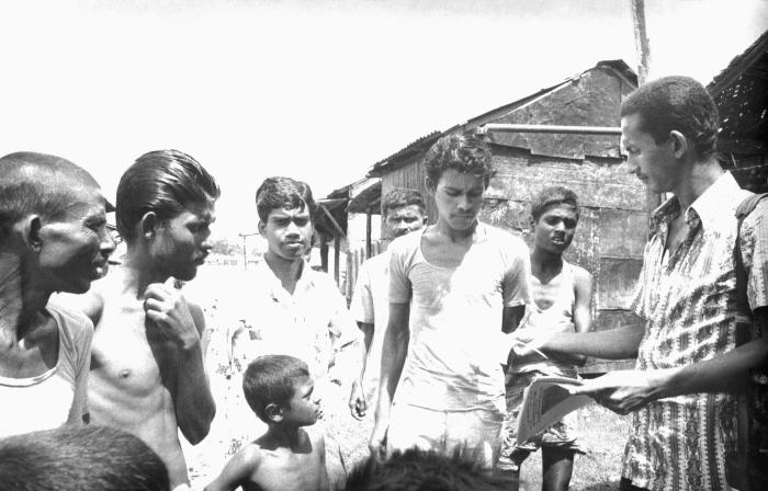 This 1975 image depicted a community volunteer smallpox eradication team member as he was handing out leaflets, which would inform residents