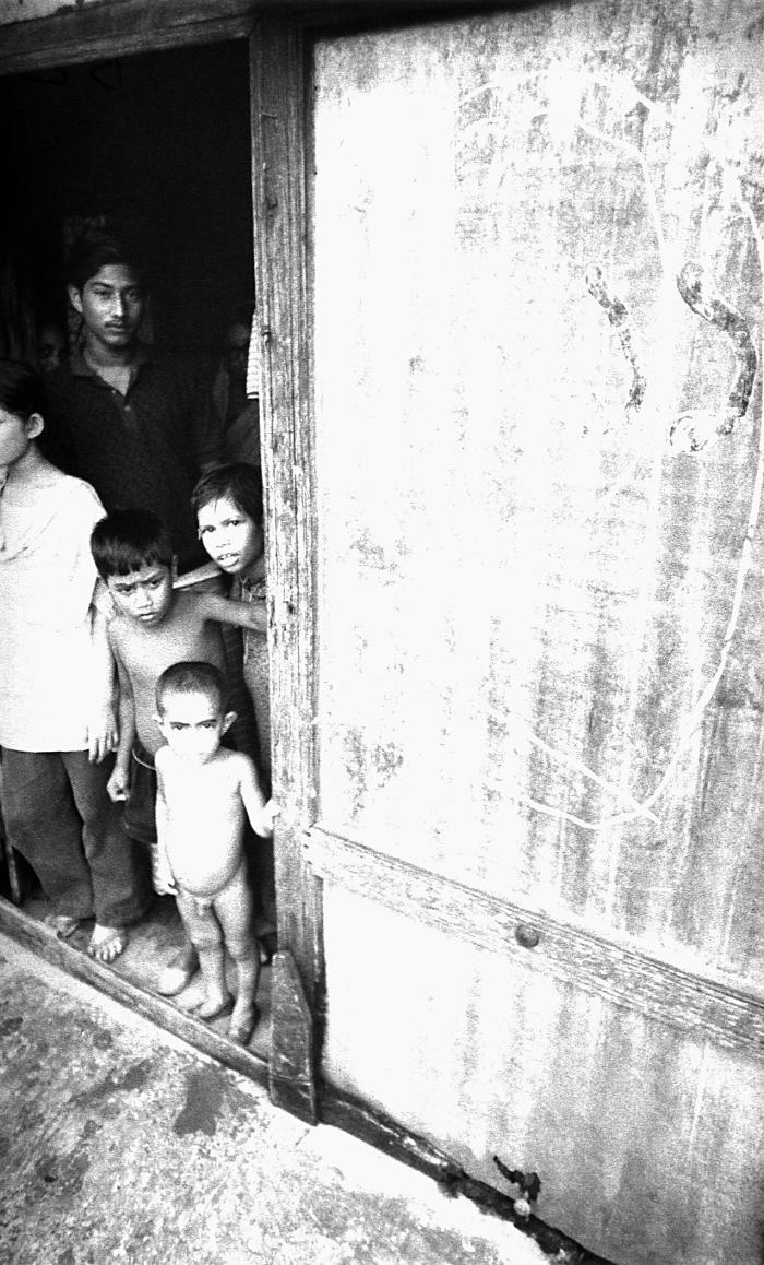 This 1975 photograph depicted a group of children standing in the doorway of a typical Bangladesh village home. It was captured as a local s
