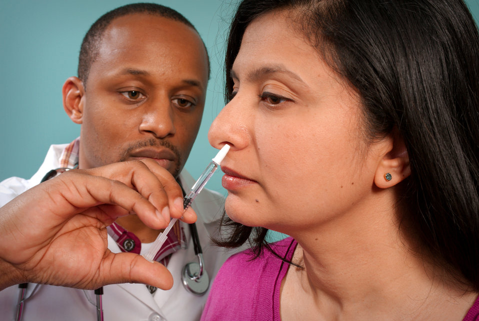 This 2009 image depicts a healthcare practitioner as he was administering the H1N1 live attenuated intranasal vaccine (LAIV) to a female rec