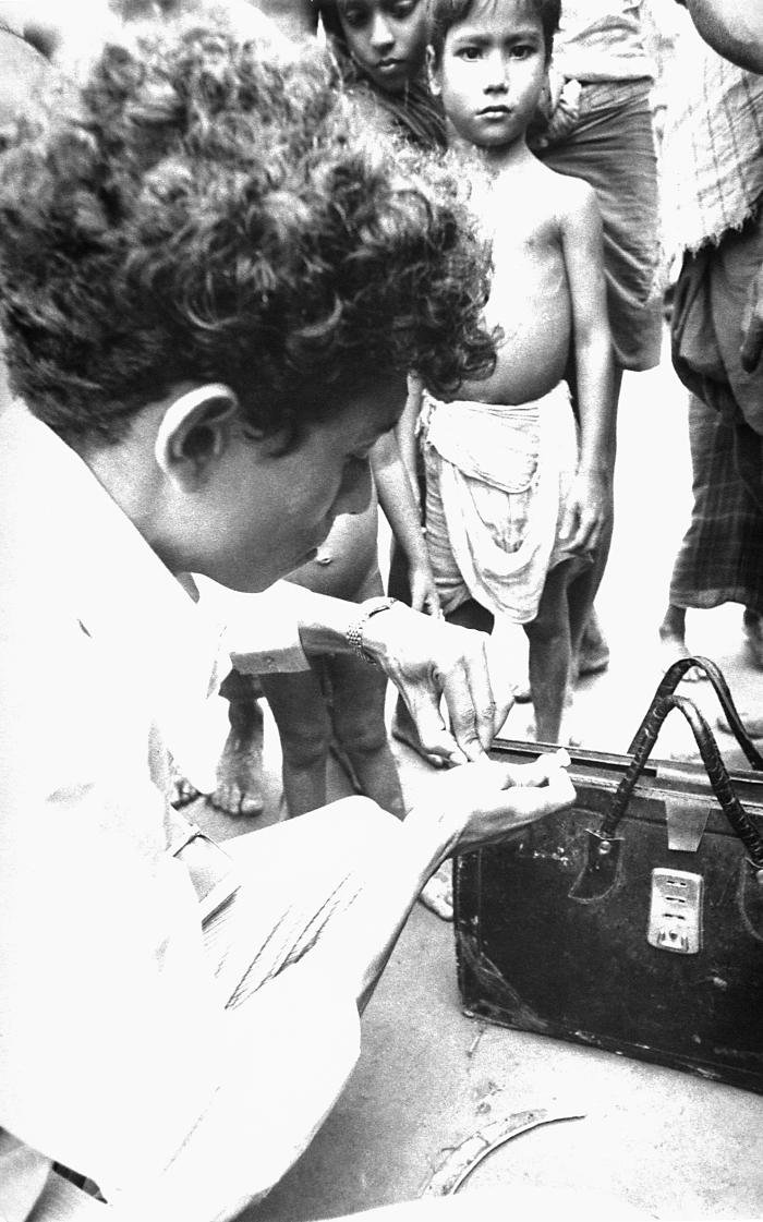 This community smallpox eradication team volunteer vaccinator was photographed as he was checking his vial of smallpox vaccine, while a smal