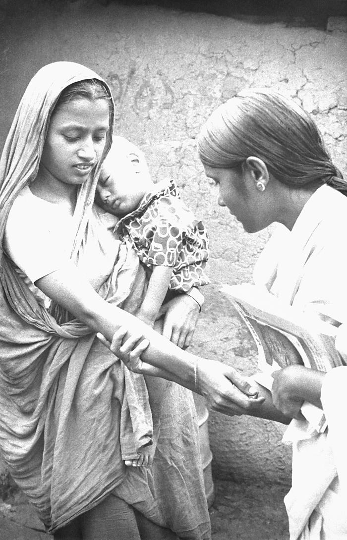 This volunteer smallpox eradication team vaccinator was in the process of checking the smallpox vaccination scar on this mother's right fore
