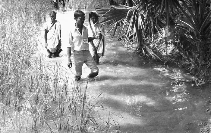 These local smallpox eradication team members were shown here slogging through the village backwaters in their quest to locate any remaining