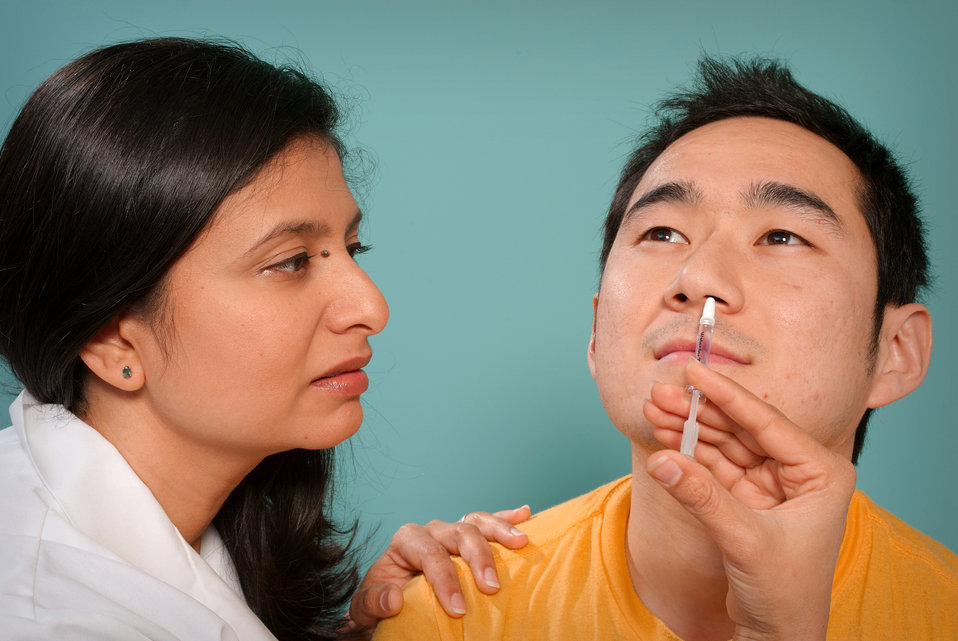 This 2009 image depicts a healthcare practitioner as she was administering the H1N1 live attenuated intranasal vaccine (LAIV) to an Asian ma