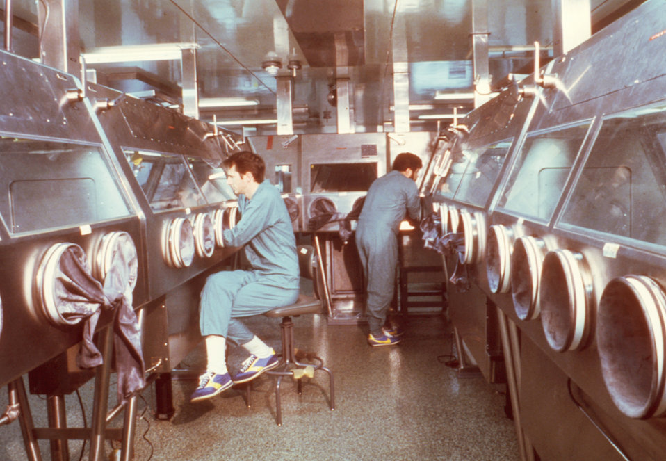 Here two CDC scientists are shown working in the specially designed Maximum Containment Lab, or BSL-4 facility.